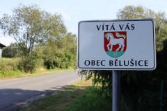 Cedule s nápisem vítá vás obec Bělušice na začátku obce